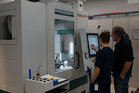 Urs Rohrer and Simon Lüthi operate the new milling machine